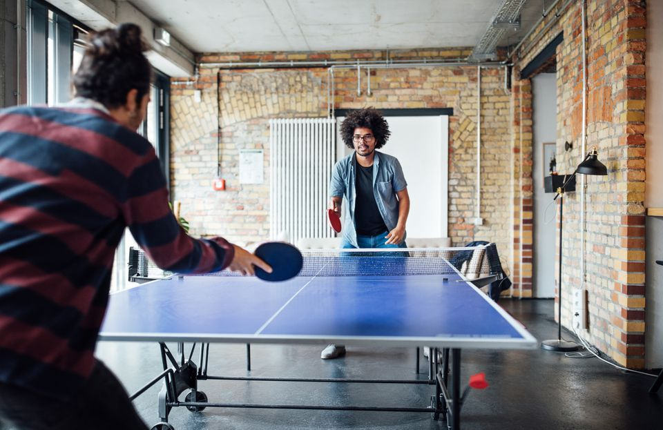 Businessmen play ping pong