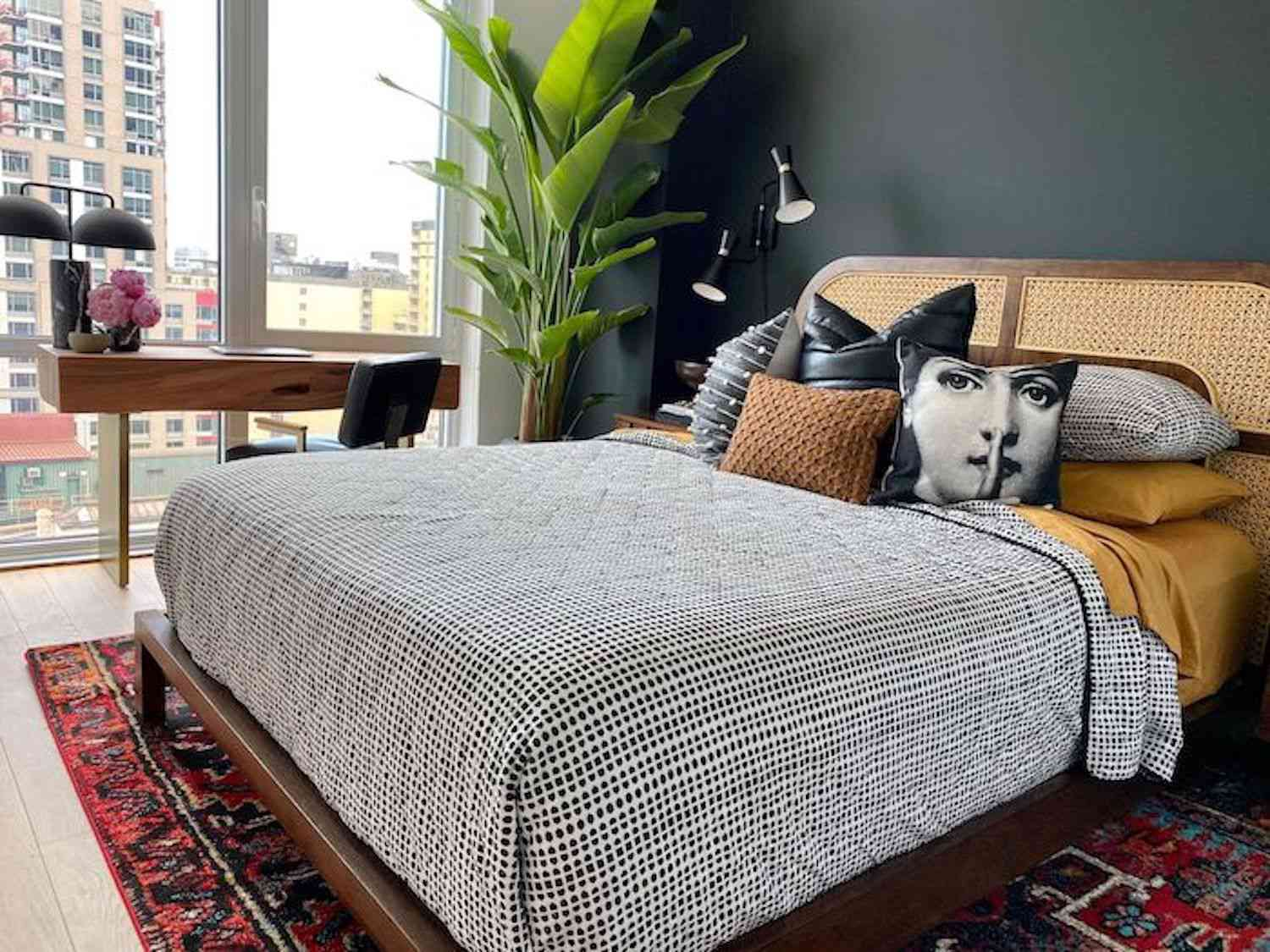 modern bedroom with wicker headboard, black and white polka dot comforter, red pattern rug, large plant in corner