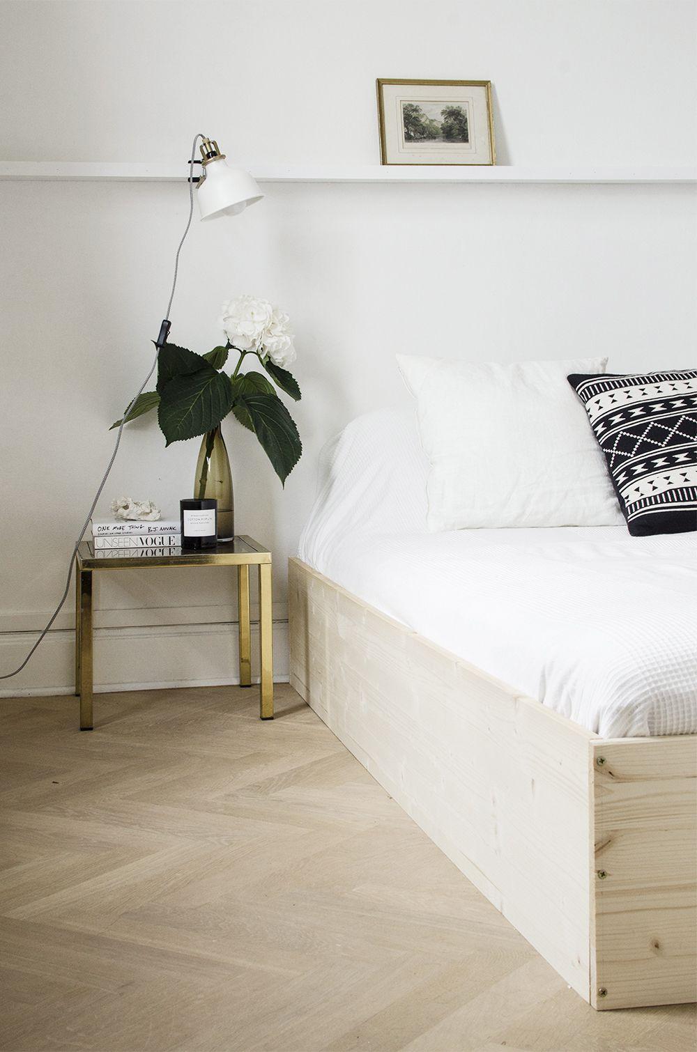 A wooden platform bed frame in a bedroom