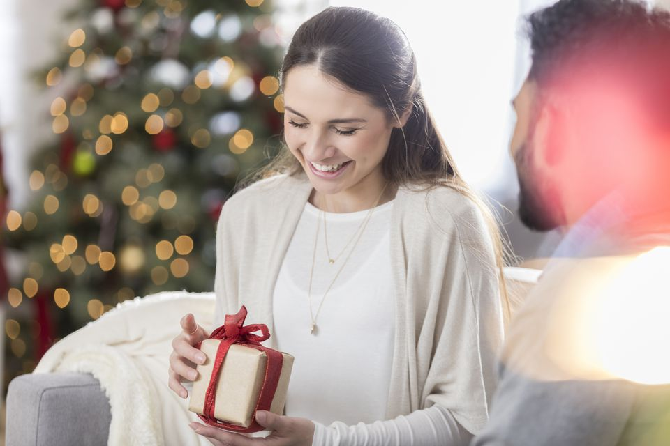 Woman enjoys opening Christmas present from her husband