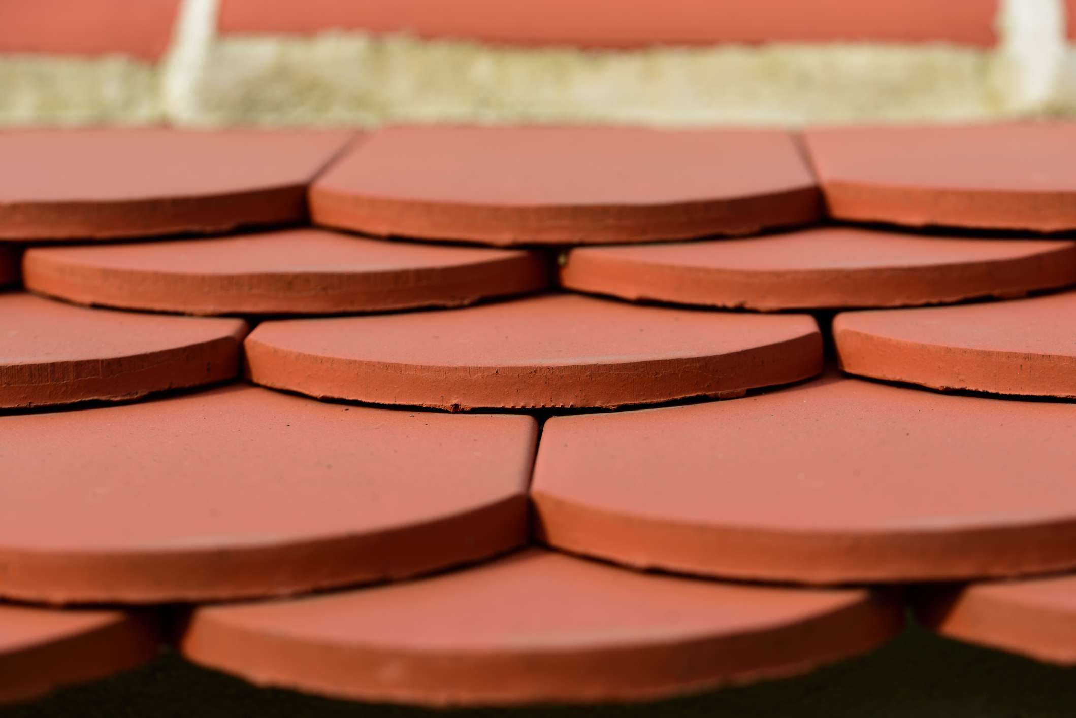 Close-up of flat red clay roof tiles layered on a roof.