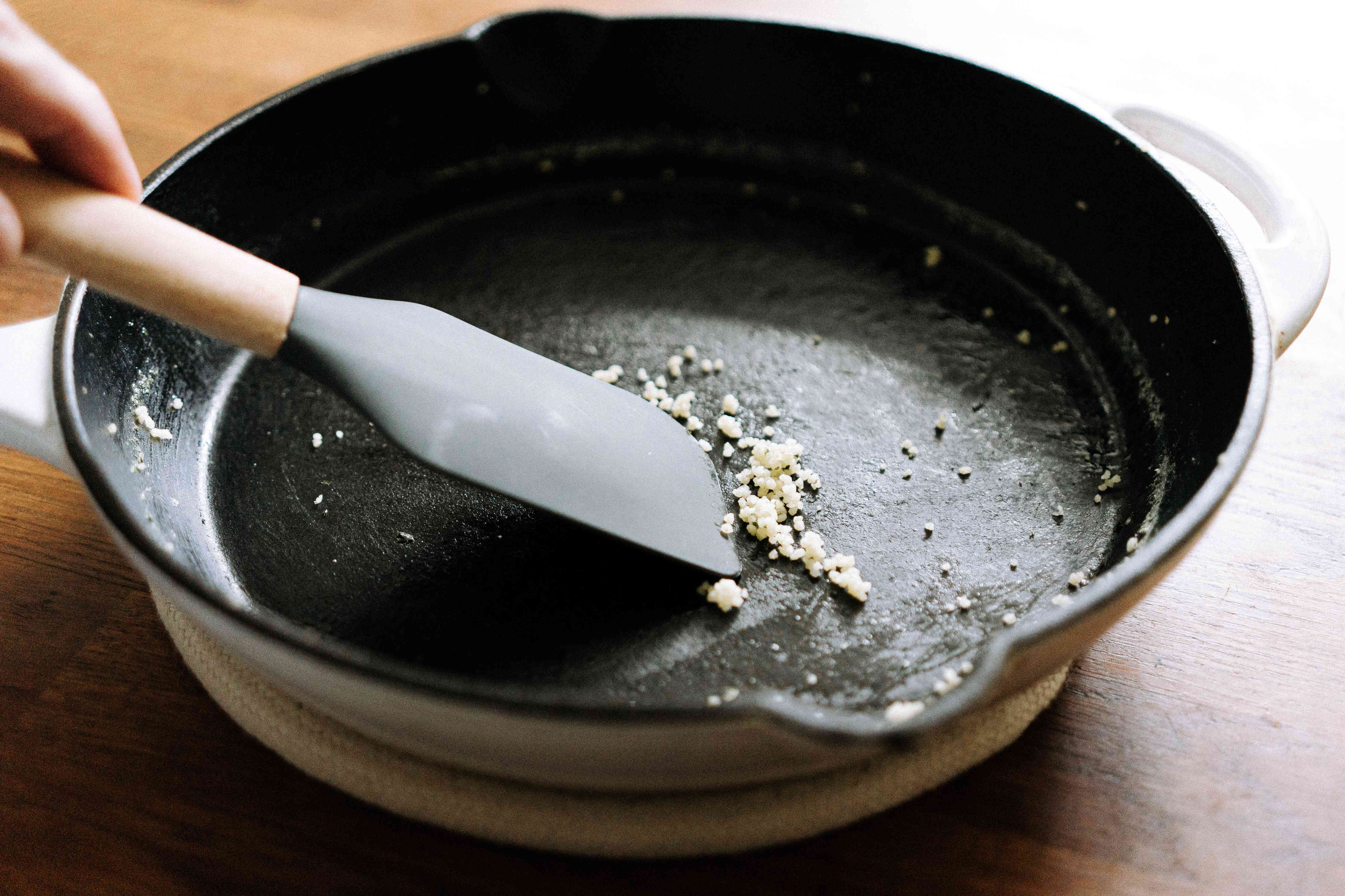 using a spatula to scrape off extra food from cast iron