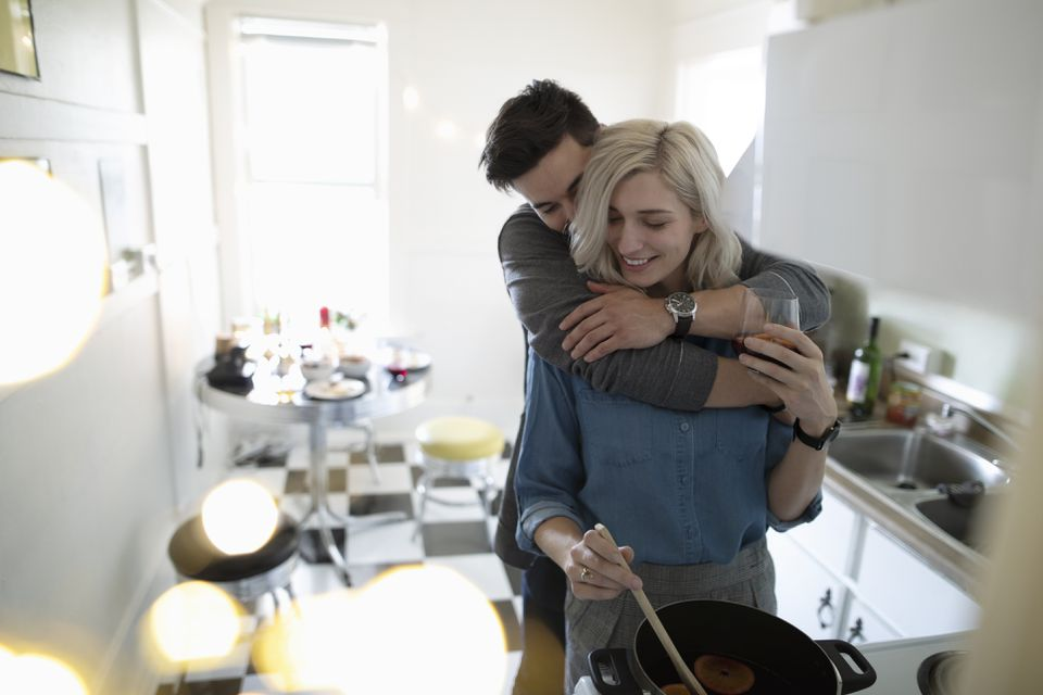 Couple hugging, cooking in apartment kitchen