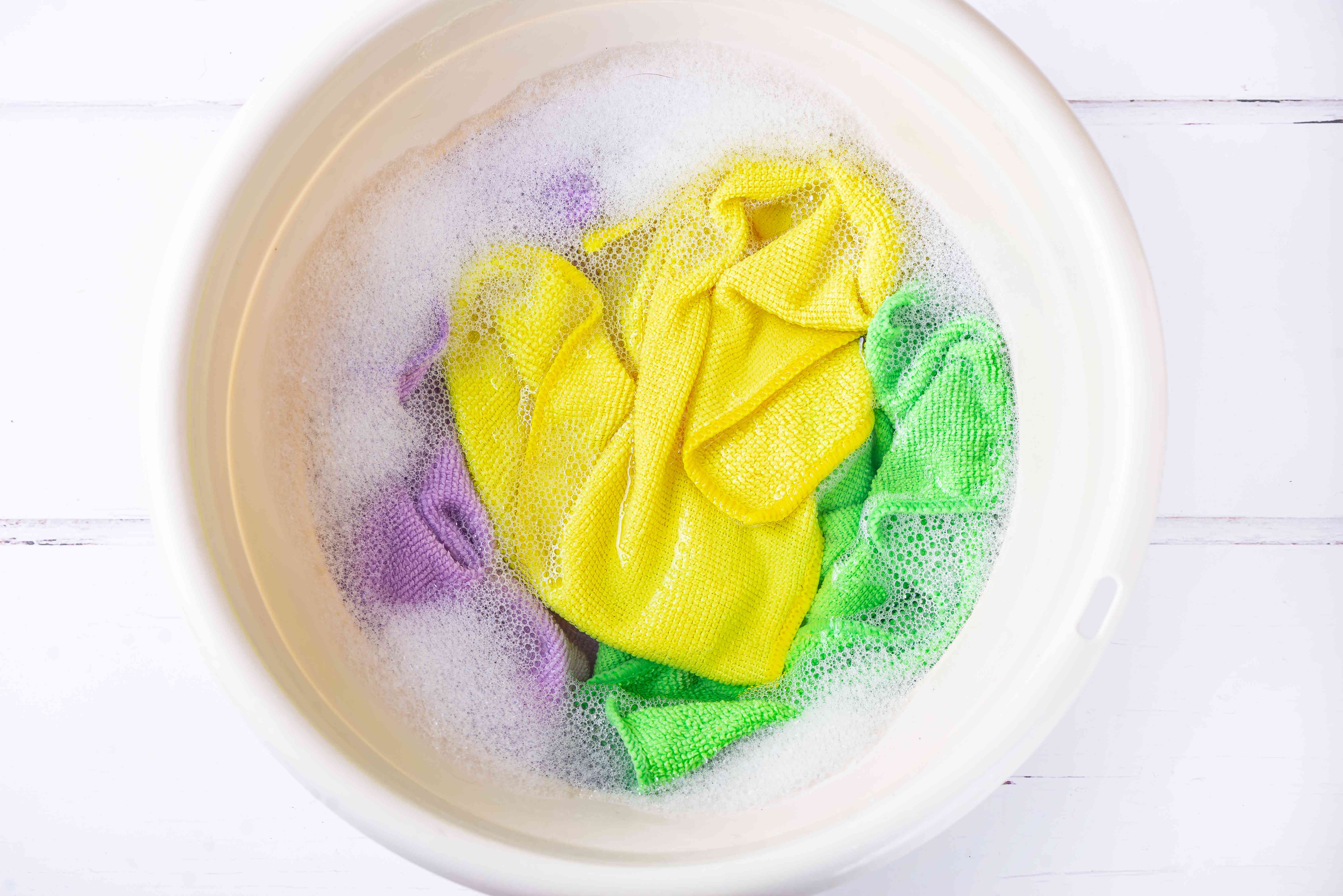Multi-colored microfiber cloths soaking in bucket with soapy water