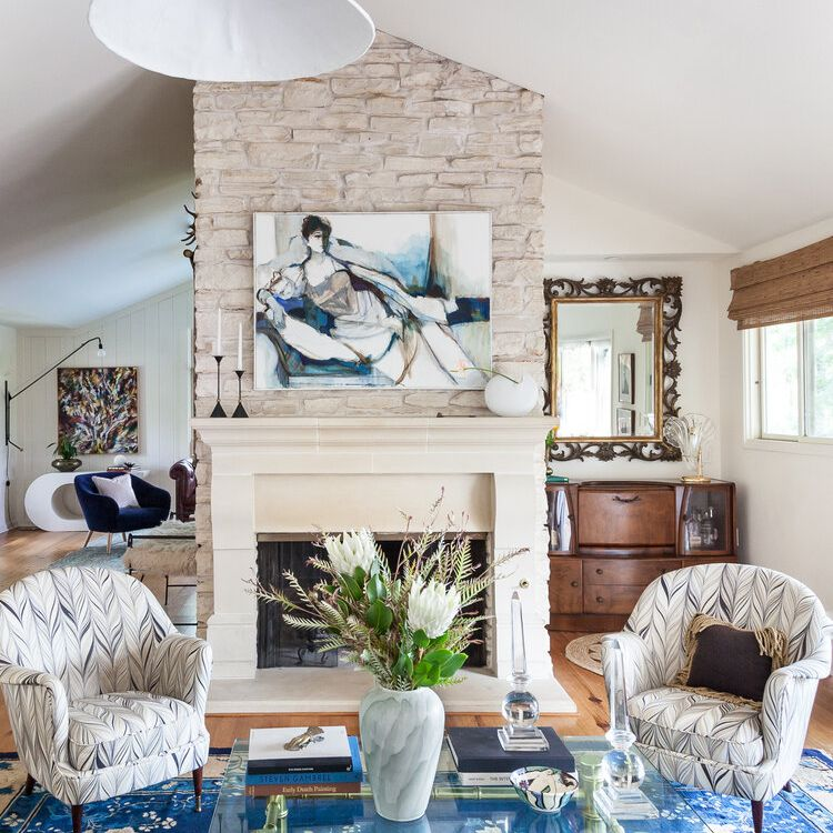 living room with large art piece above fireplace