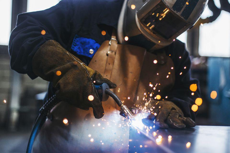 Welder in helmet welding with sparks flying