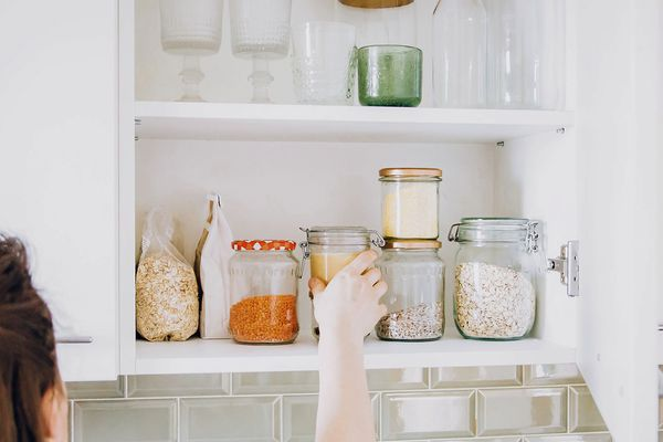 woman putting jars back into cabinets