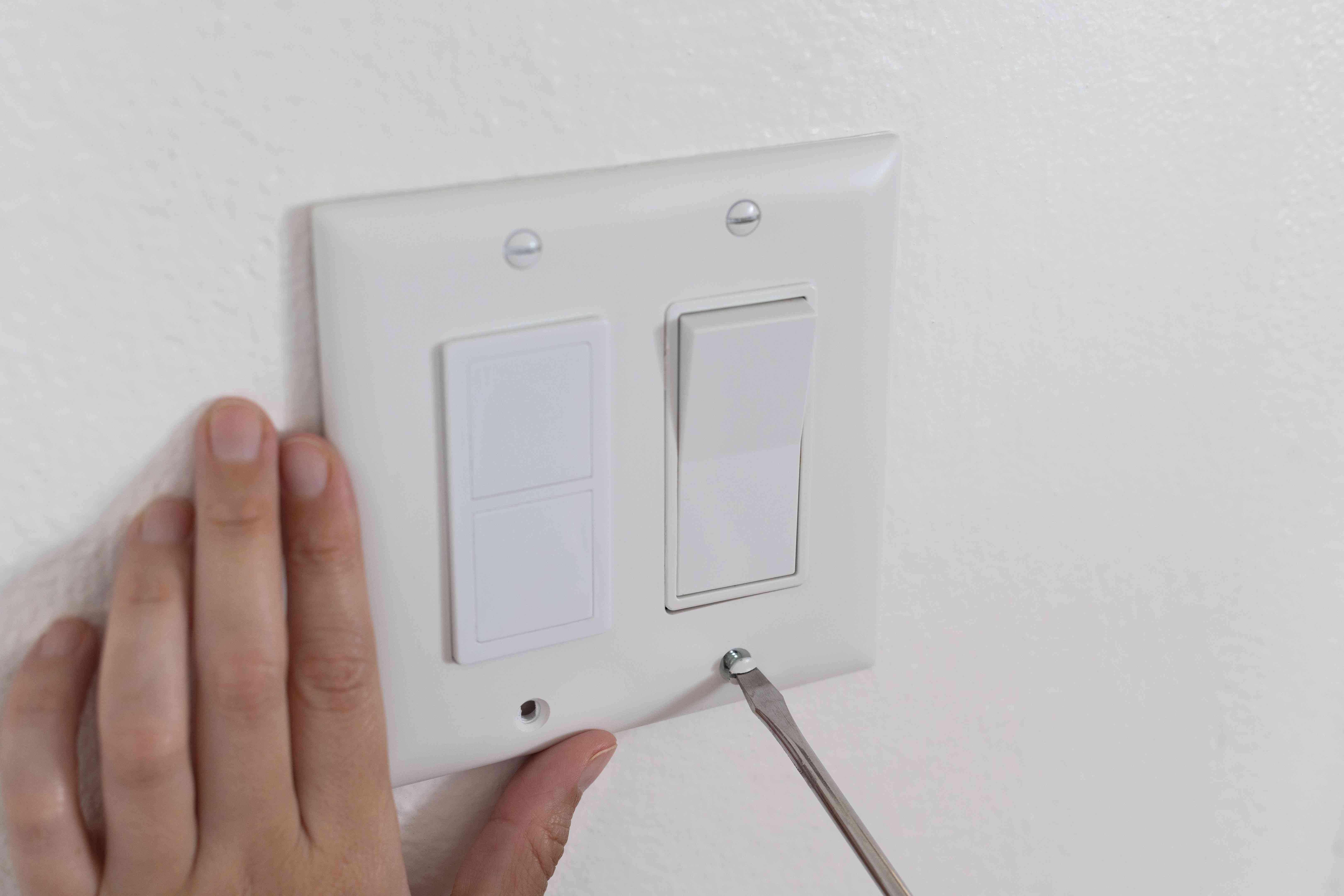 Electrical outlet being removed to insert insulate