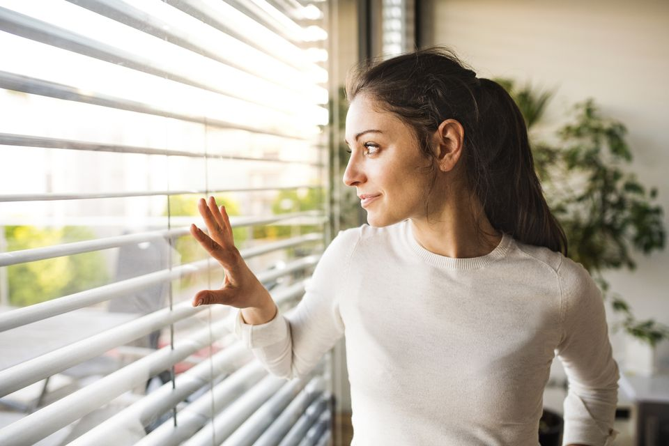 woman looking out blinds