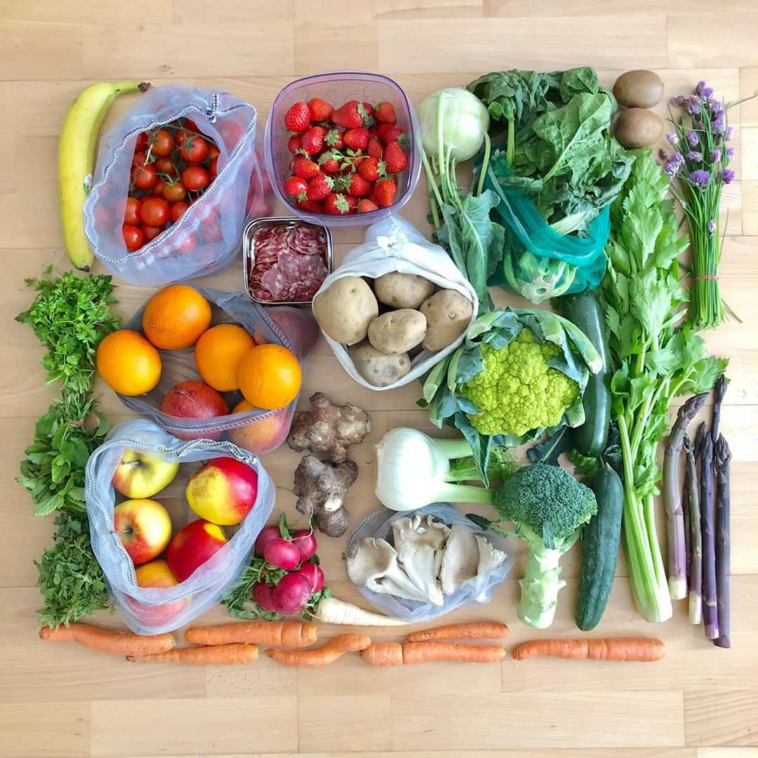 An assortment of vegetables and fruits on a wood background