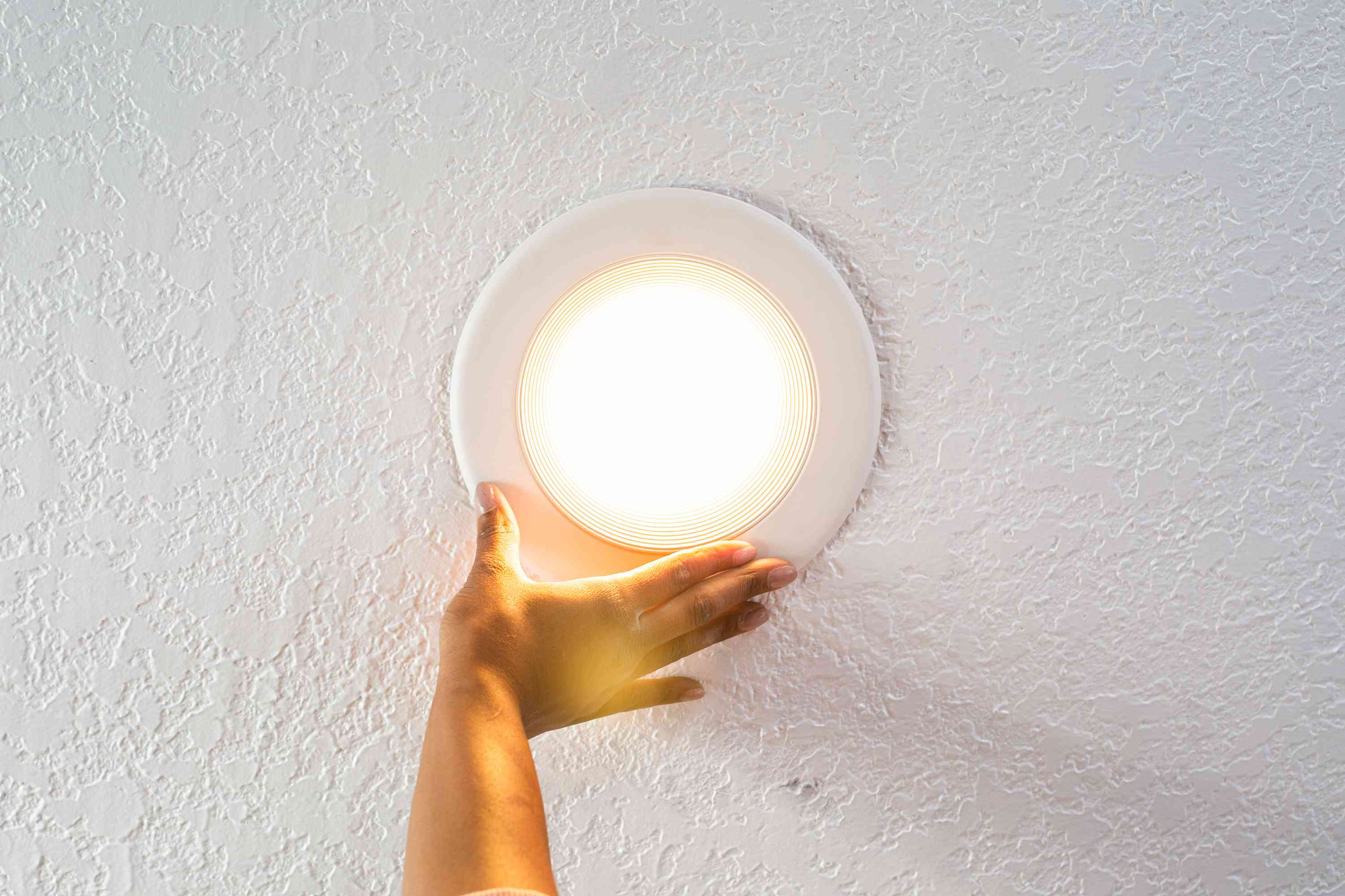 Recessed lighting held up by hand with light turned on