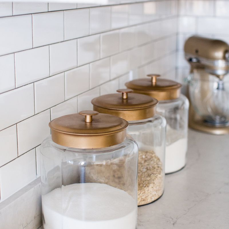 Glass and copper kitchen canisters against a white tile wall