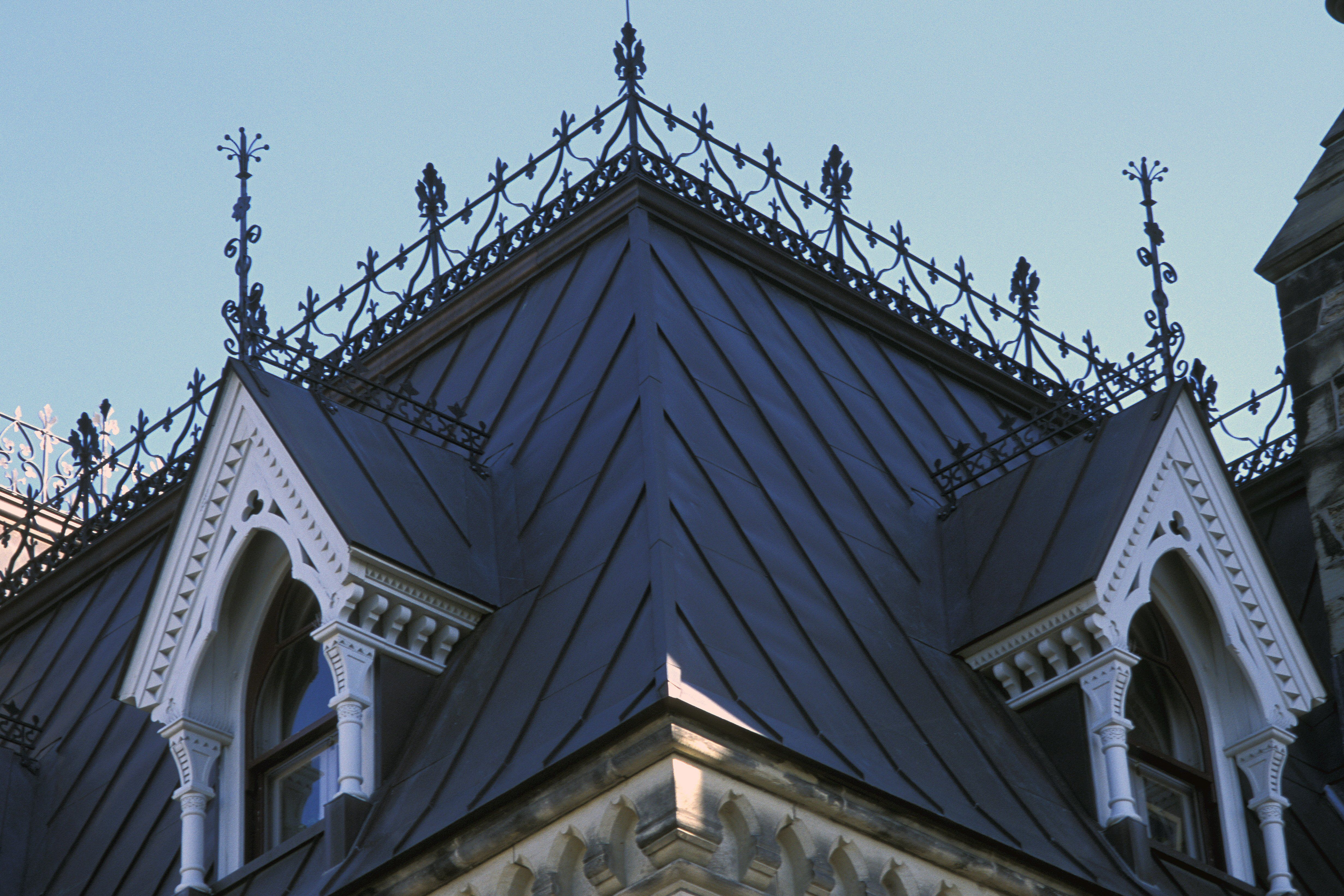Detail of ornate gabled dormer windows from the steep slope of a mansard roof