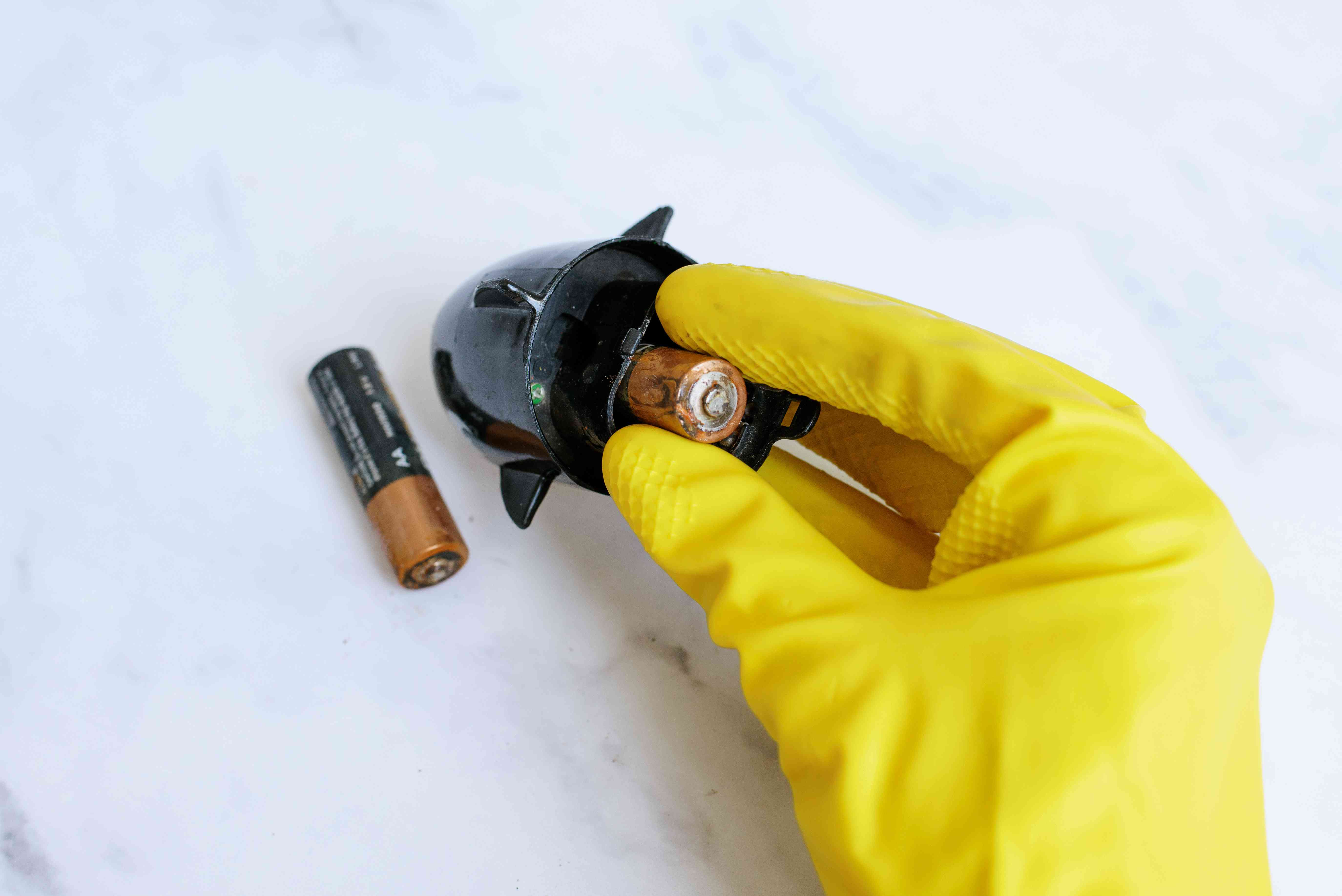 Batteries with corrosion removed from device with yellow gloves