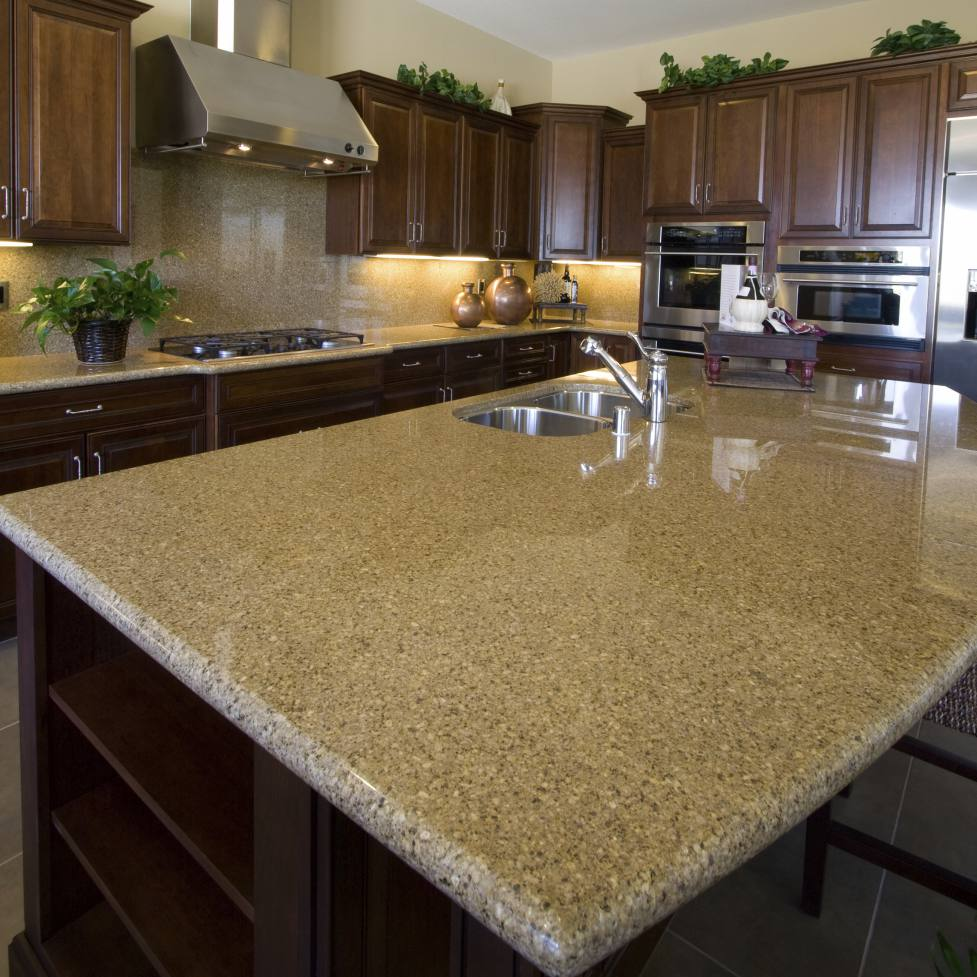 a common beige granite on an island in a cherry wood style kitchen