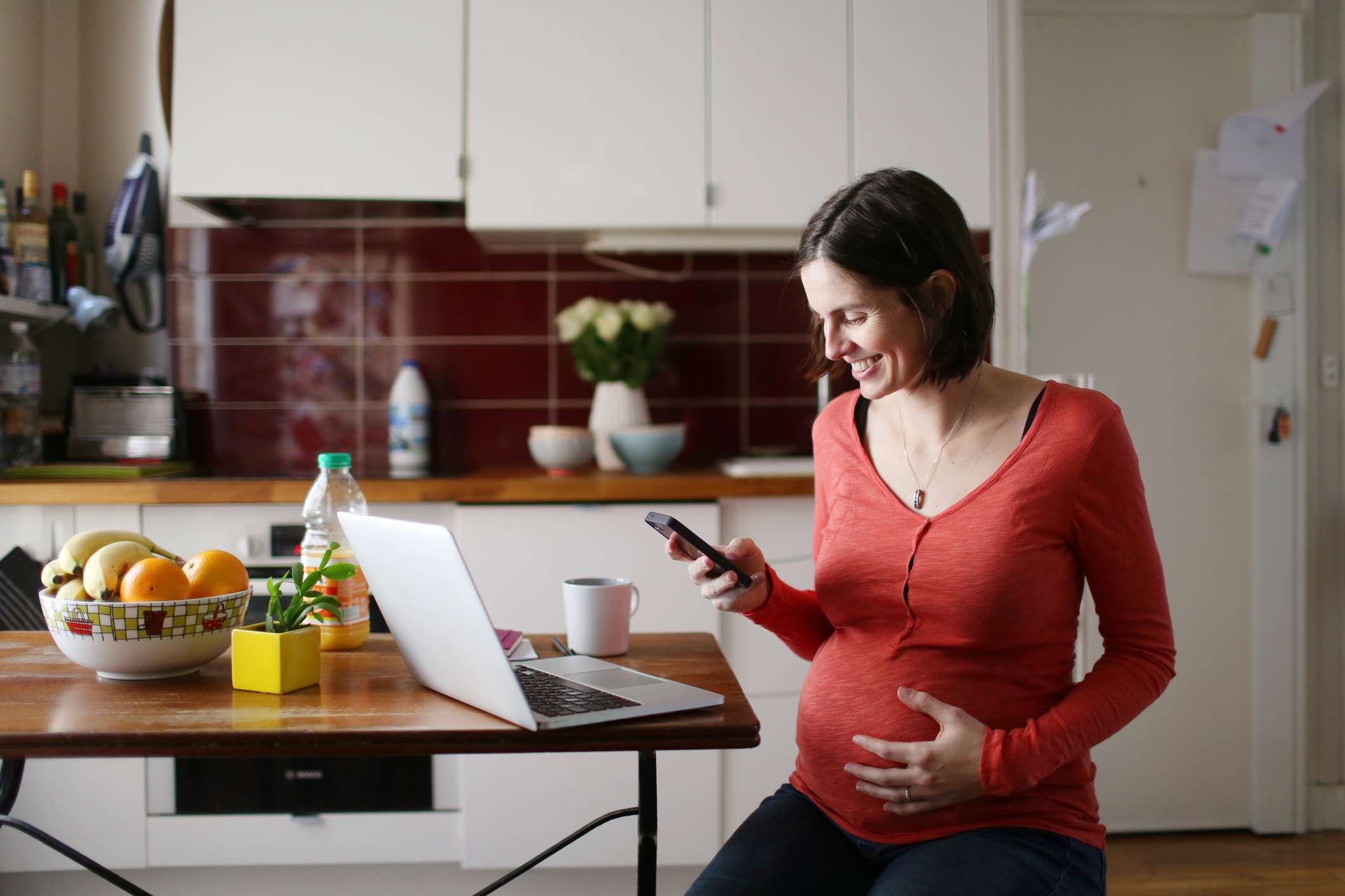 A pregnant woman looking at her phone