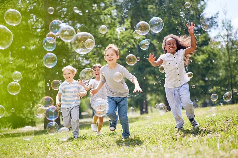 Multi-ethnic kids playing in bubbles