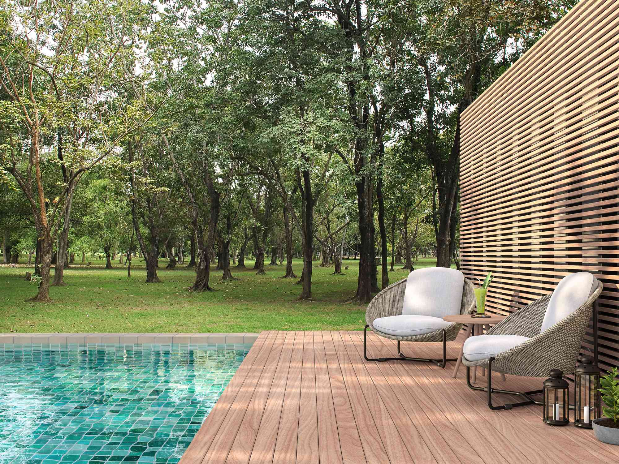 A backyard pool surrounded by a tall wood wall, a wood deck and lounge chairs.