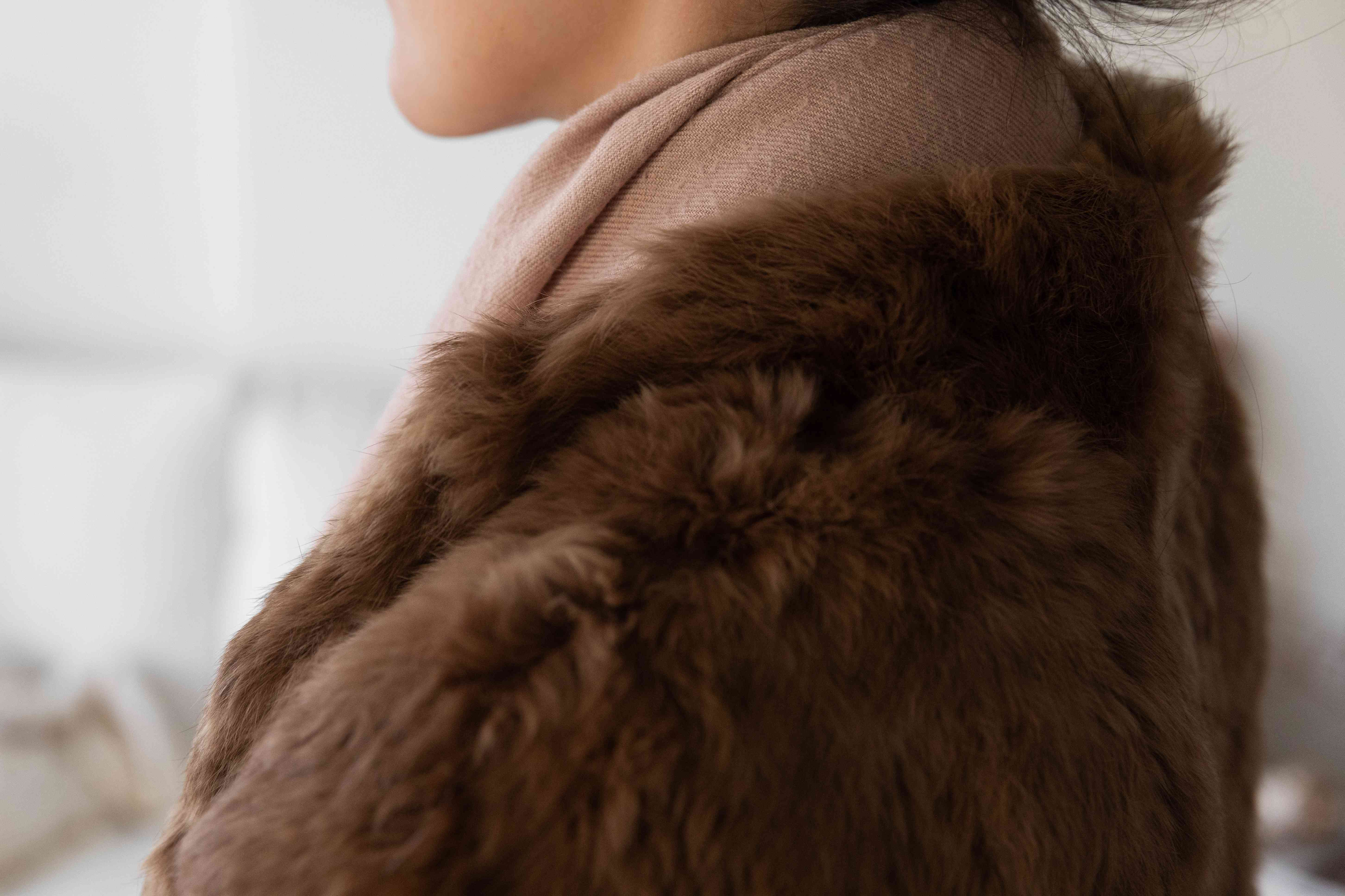 Someone wearing a scarf with a fur coat