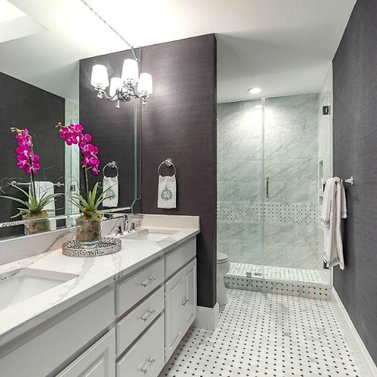 Galley bathroom with dark walls and white floor and cabinets.
