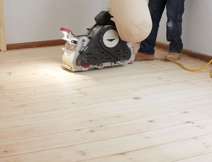 Sander machine with cord passing next to person standing on hardwood floor
