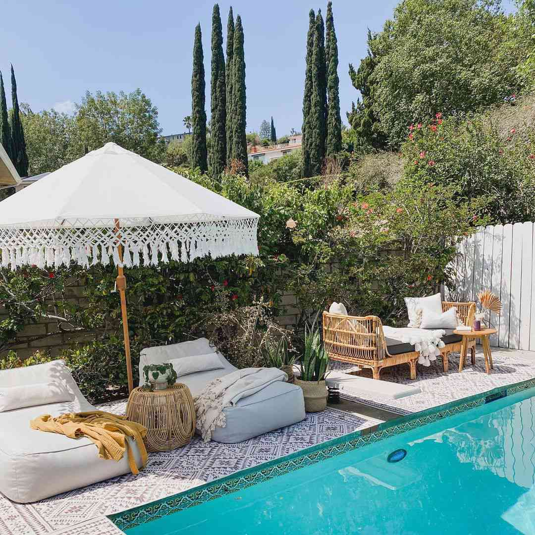 A Bohemian style pool area with a large umbrella, rugs and lounge chairs.