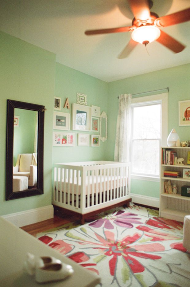 Mint green nursery with bold floral rug.