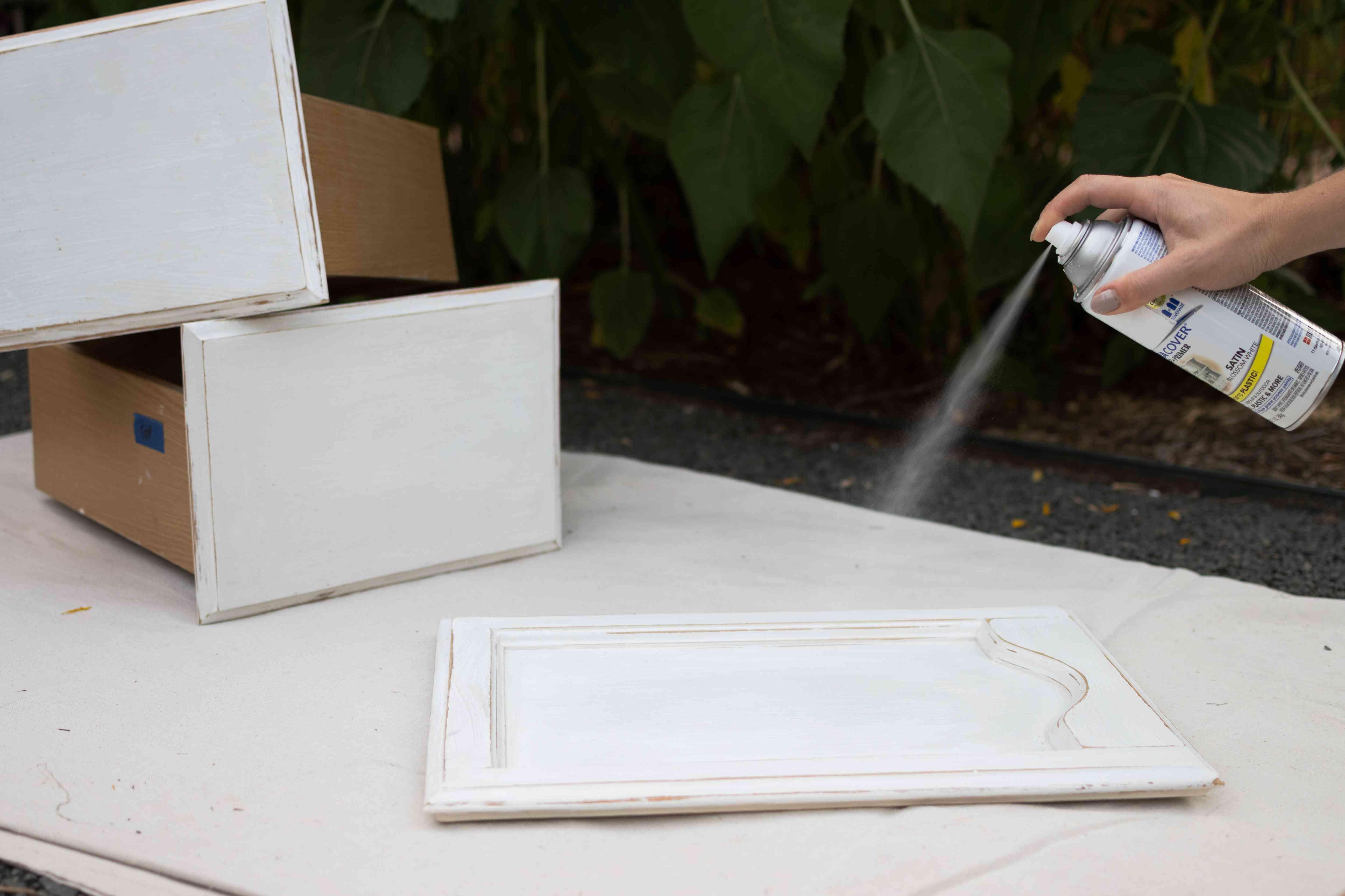 Primer sprayed on bathroom cabinet doors outside on white sheet