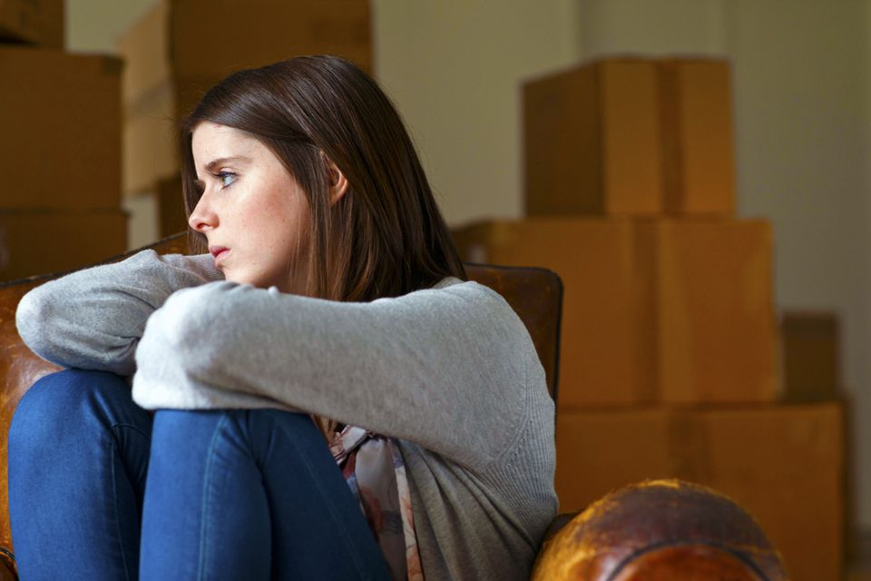 Woman feeling sad with packed moving boxes