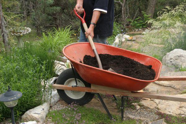 Man with a wheelbarrow full of soil