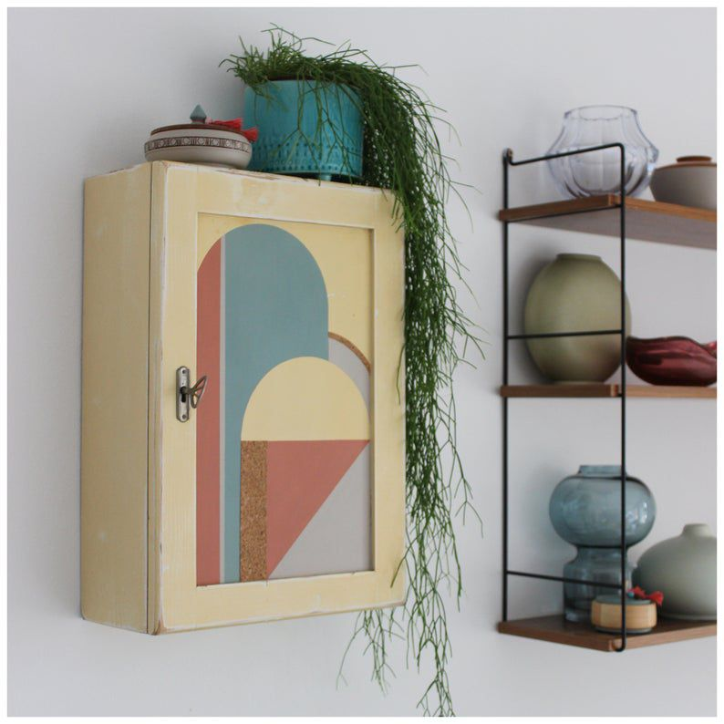 a hanging cabinet features neutral colors and a plant on top