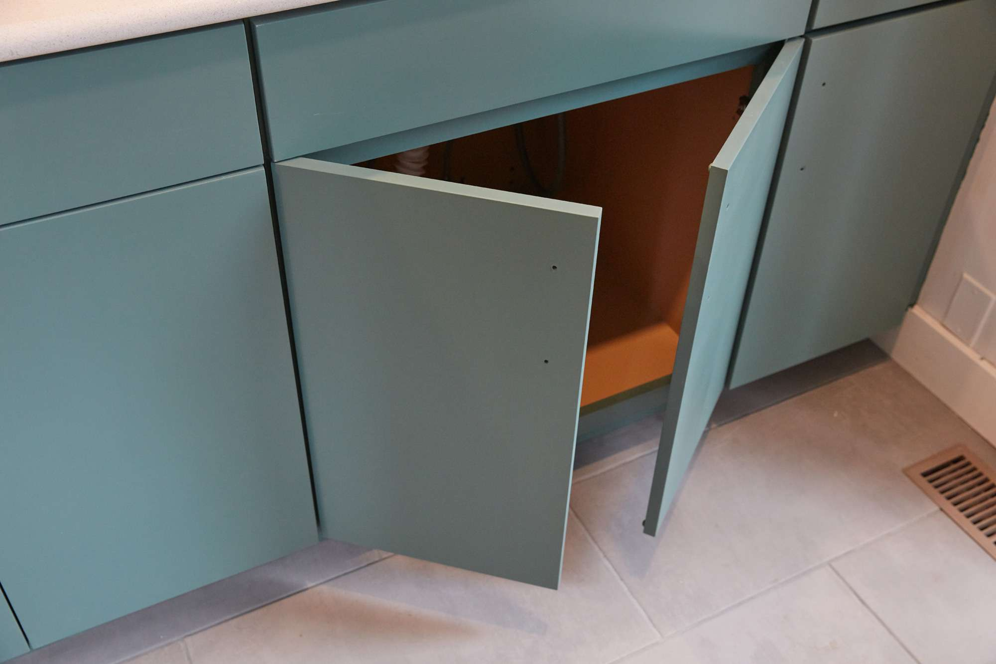 Newly installed mint green kitchen cabinets with doors open