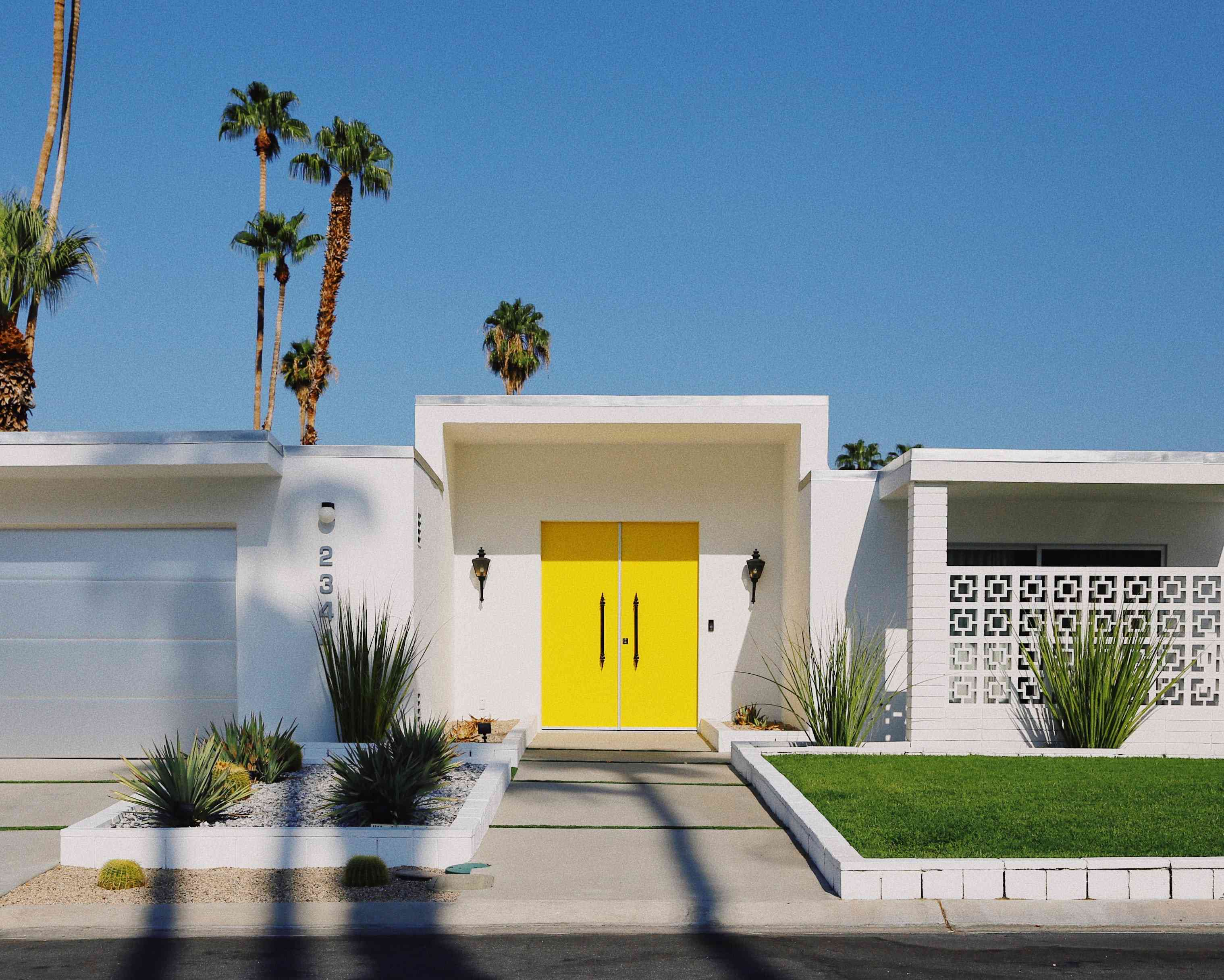 white house with yellow front door against a blue sky with palm trees