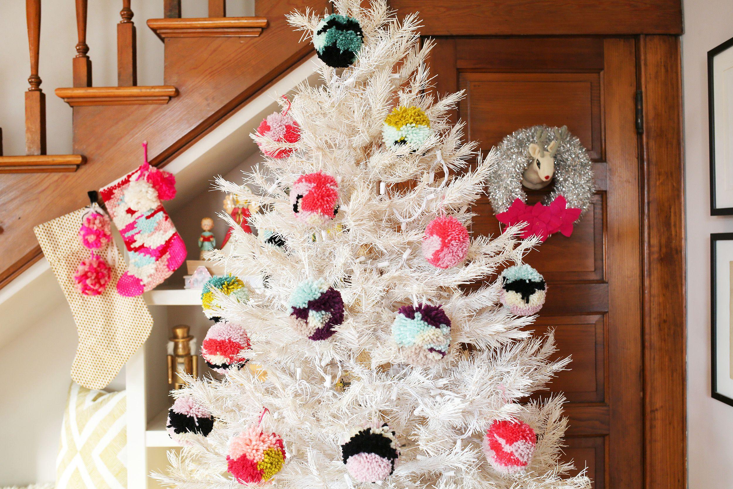 Árbol de Navidad blanco con adornos de pompones cerca de escaleras de madera