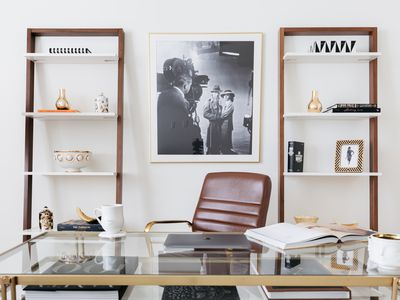Home office with leaning wooden and white book shelves with glass desk and brown leather chair