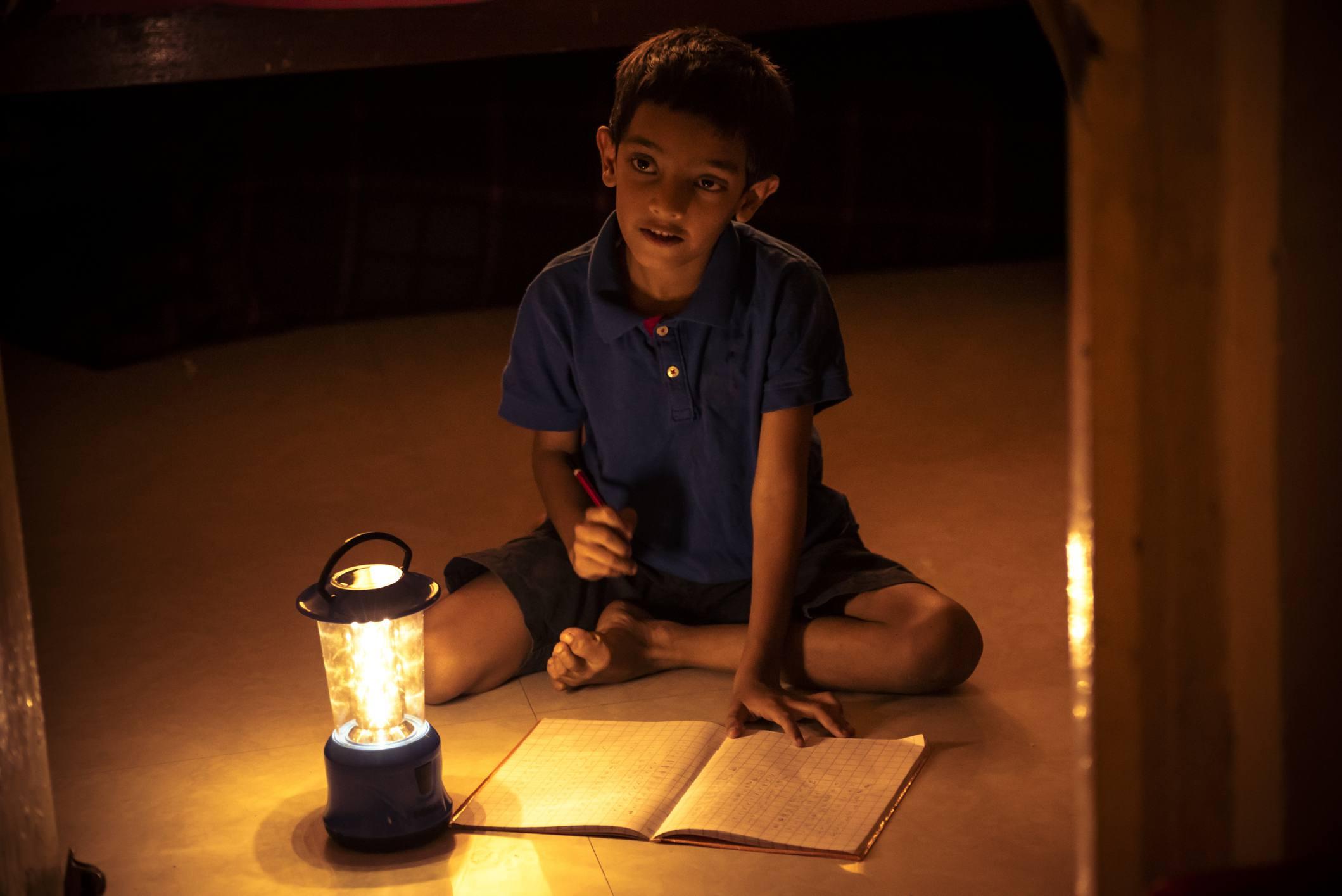 Boy writing in notebook under light of solar lantern