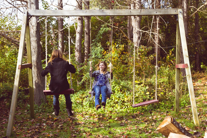 teens on old swingset in yard