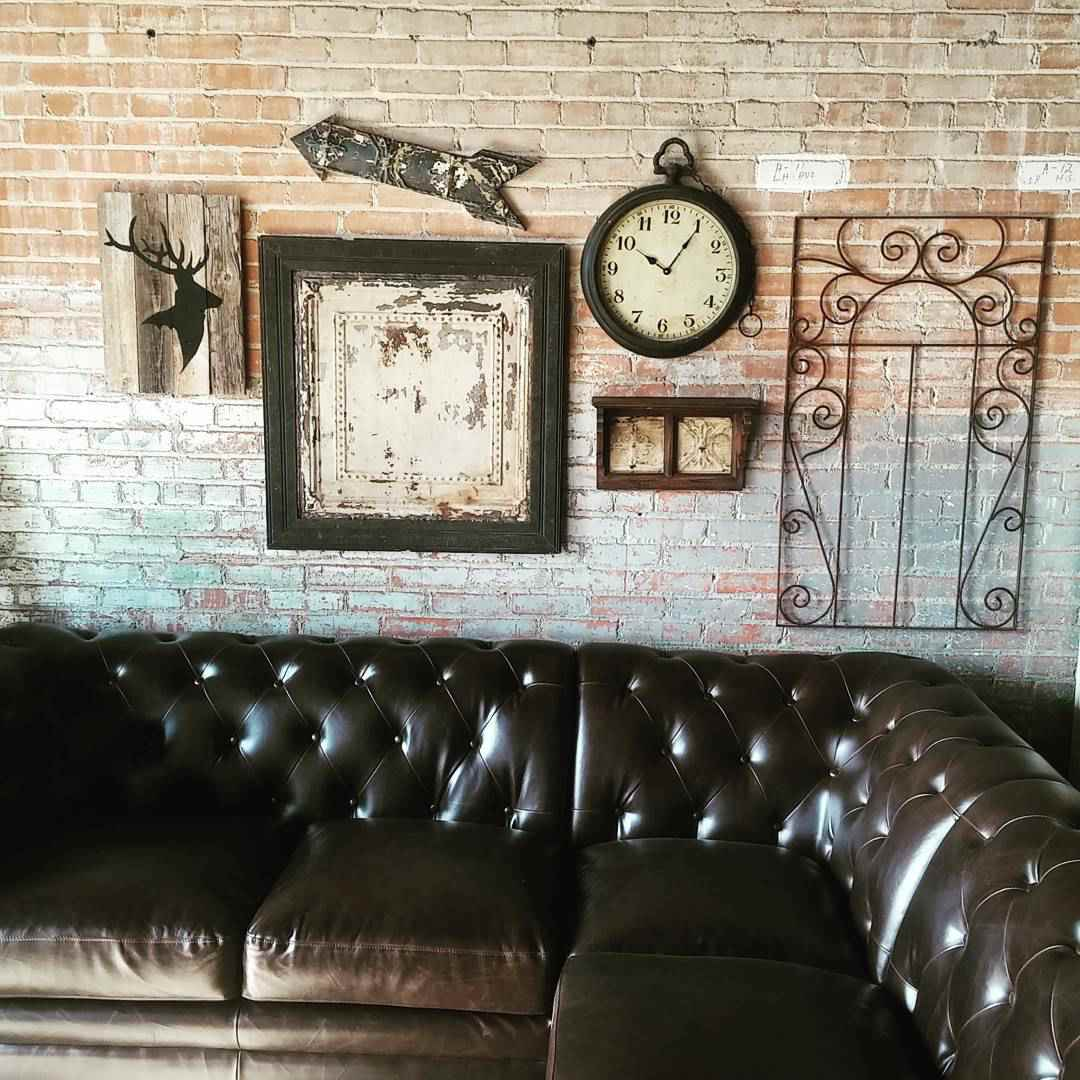 Vintage tin pieces hanging on the wall above a leather couch.
