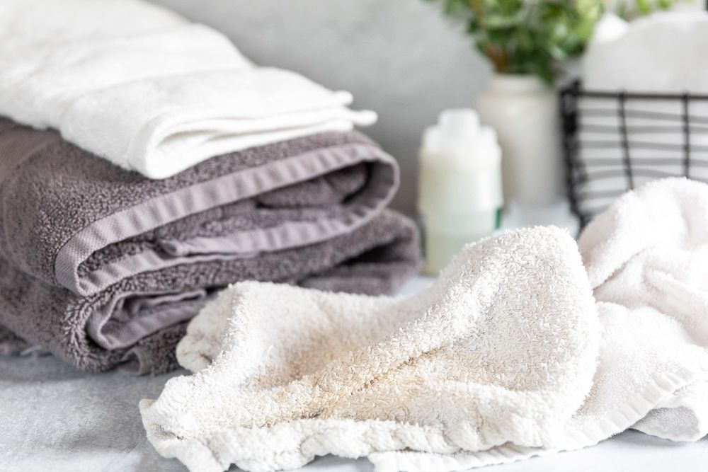 Crumpled white towel with brown stain in front of folded clean towels