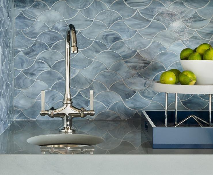 protector contra salpicaduras de mármol azul en forma de baldosas onduladas detrás de un fregadero plateado