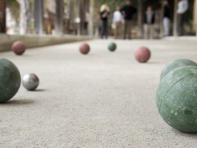 People playing bocce ball, balls in focus in foreground