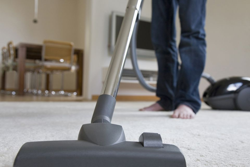 Man vacuuming carpet