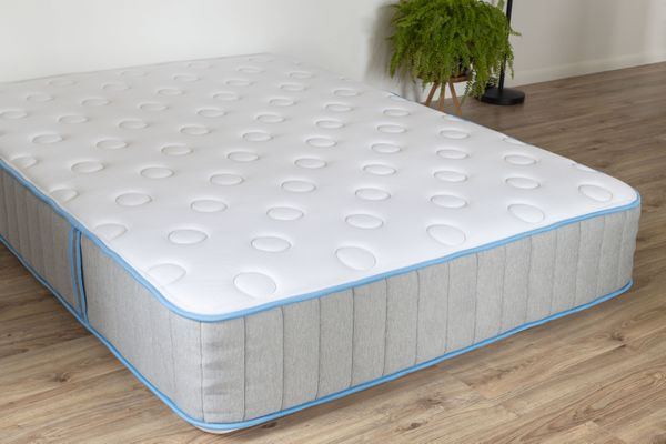 New mattress lying on wooden floor next to houseplant to be stored