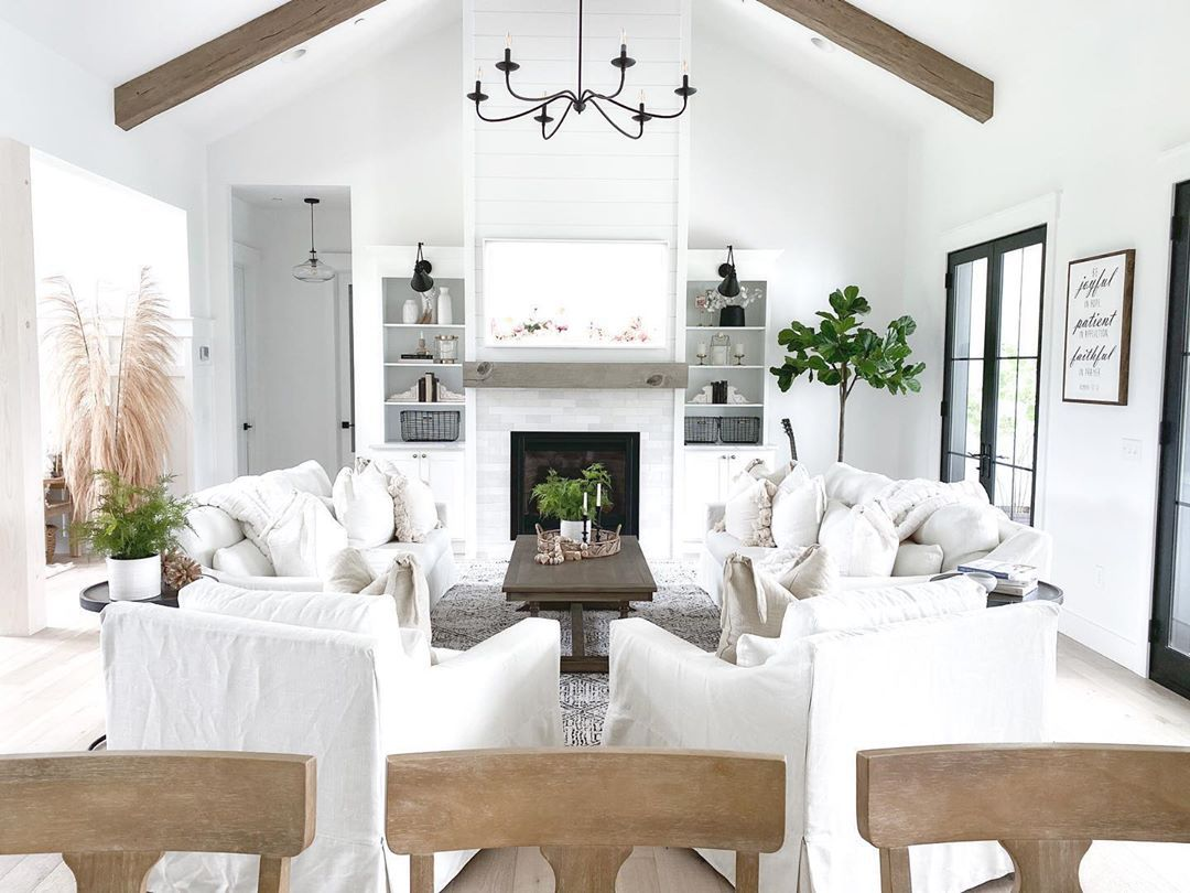 Living room with white couches and wood beams