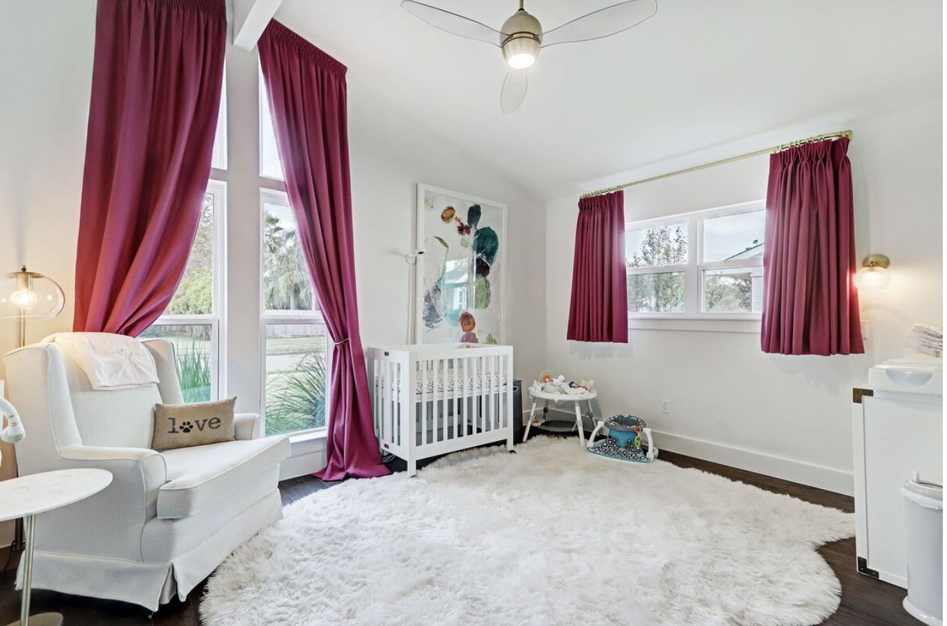 nursery with long and short pink curtains in a white color scheme