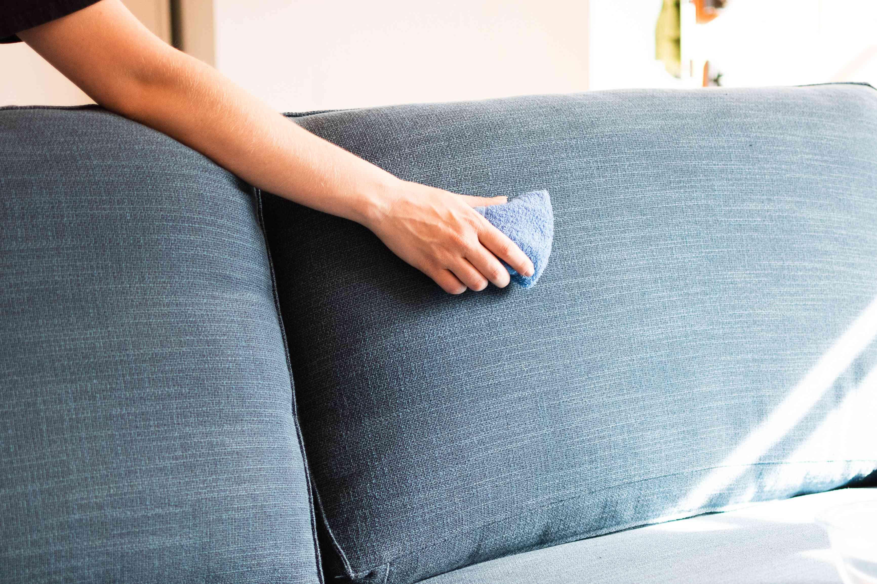 Bọt biển nhúng trong dung dịch làm sạch đi qua đệm sau của ghế dài bọc nệm