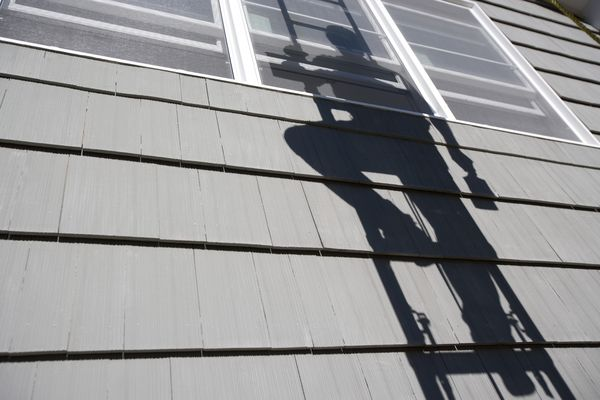 House shingles with the shadow of a painter on a ladder