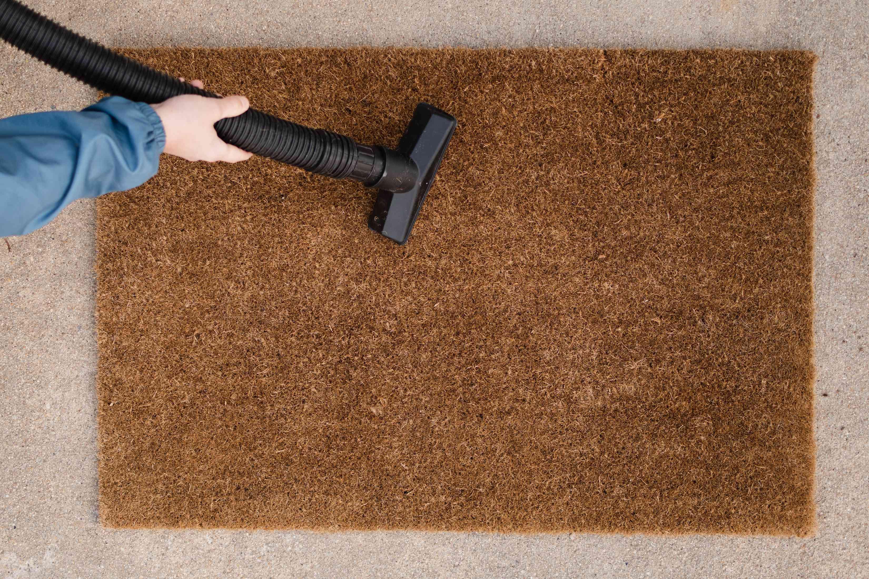 Black vacuum hose passing over brown doormat for deeper cleaning