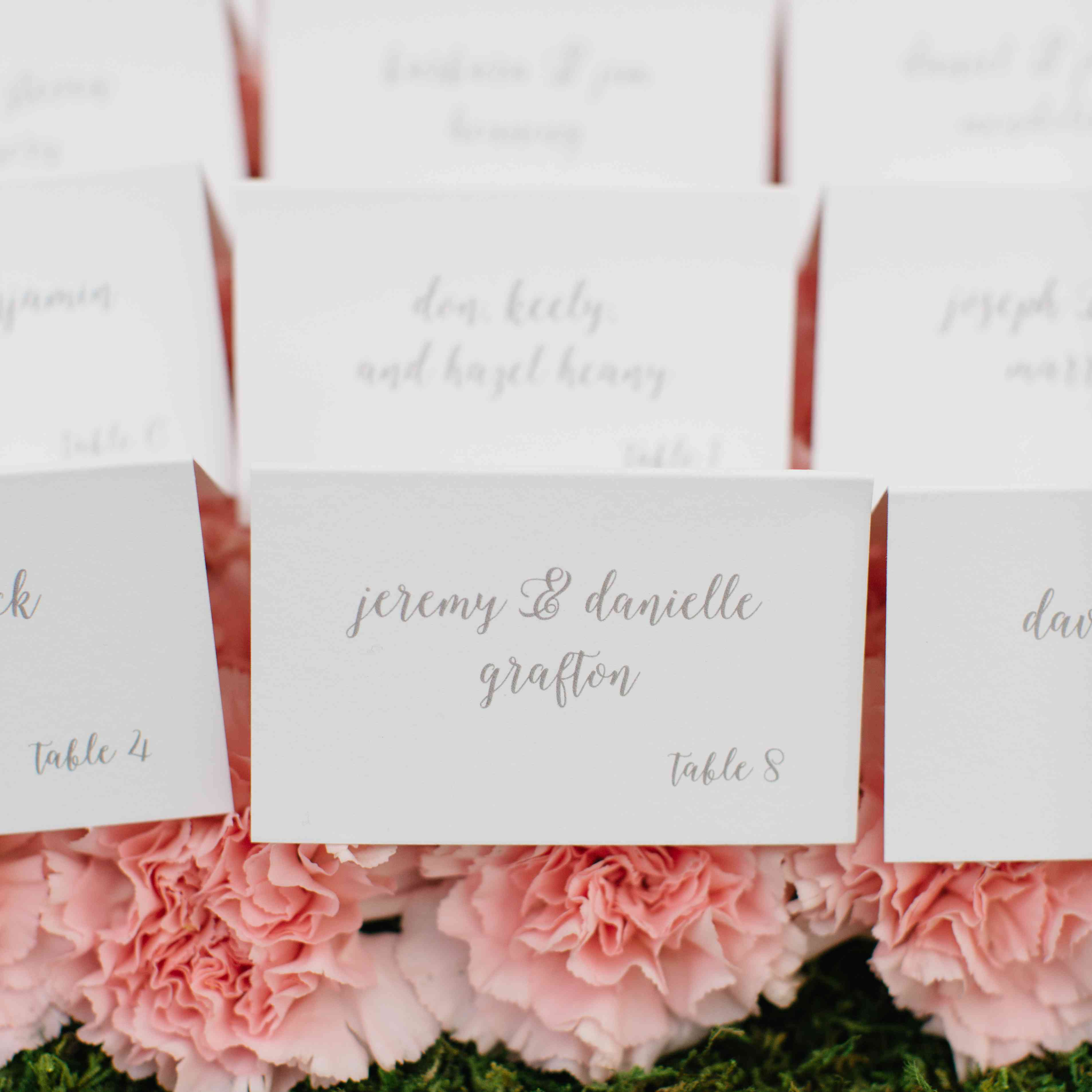 Classic escort cards on top of flowers
