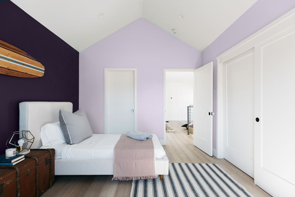 Decorated bedroom with light purple accent wall behind white bed and white closet doors